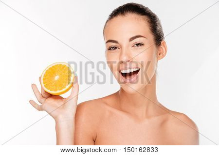 Joyful young woman holding juicy orange isolated on a white background