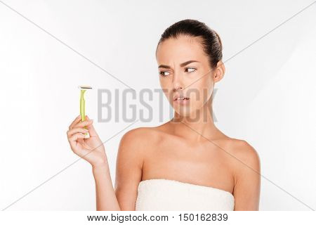 Young beautiful woman with pure skin in a towel biting lip and holding razor blade preparing to shave isolated on white background