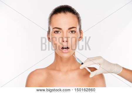 Scared young woman looking having beauty injection with syringe isolated on white background