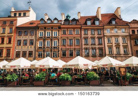 Warsaw Poland - May 28 2015: Traditional cafe with tourists against typical old houses on Old town Market square in Warsaw in a summer Poland