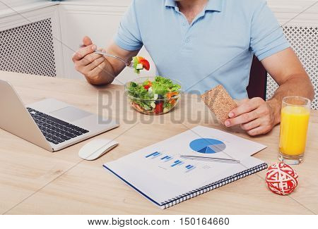Unrecognizable man has healthy business lunch in modern office. Businessman in t-shirt at working place near laptop and papers, with vegetable salad in bowl, diet and eating right concept.
