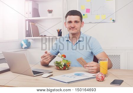 Man has healthy business lunch in modern office interior. Young handsome businessman in casual at working place, look at camera with vegetable salad in bowl, diet and eating right concept.