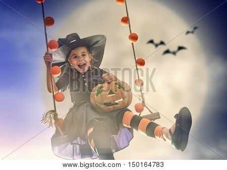 Happy Halloween! Cute little witch on swing in night. Beautiful young child girl in witch costume outdoors.