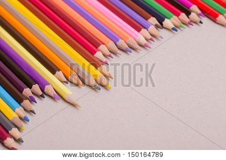 Wooden colorful pencils, on a grey paper