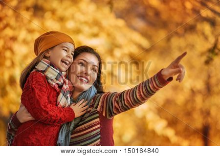 Happy family on autumn walk! Mother and daughter walking in the Park and enjoying the beautiful autumn nature.