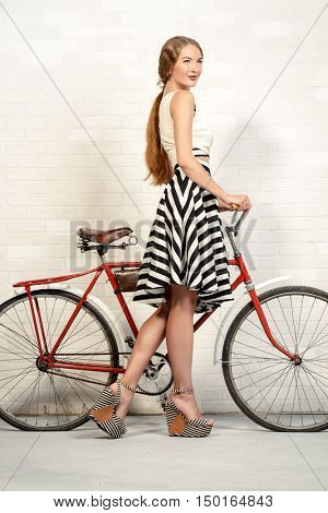 Romantic summer girl with her bicycle. Beautiful young woman wearing pretty skirt and top blouse. Fashion studio shot.