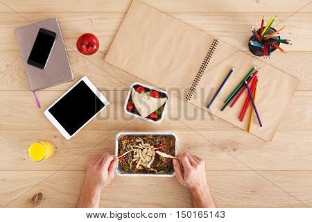 Business lunch at working place. Businessman in office. Hands of eating man. Healthy, diet food, glass noodles funchosa salad, sandwich and juice. Notebook, tablet and pencils. Top view, flat lay