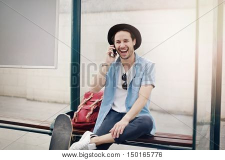 Happy young man waiting at the bus stop