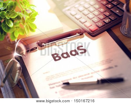 BaaS on Clipboard. Wooden Office Desk with a Lot of Business and Office Supplies on It. 3d Rendering. Blurred and Toned Image.