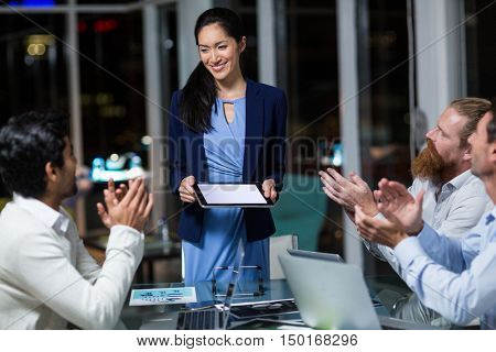 Coworkers applauding a colleague after presentation in the office