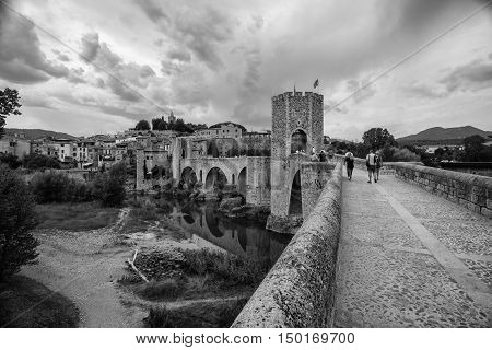 BESALU, SPAIN - AUGUST 17, 2016: People on the bridge of Besalu. The town's most significant feature is its 12th-century Romanesque bridge over the Fluvia river, which features a gateway at its midpoint.