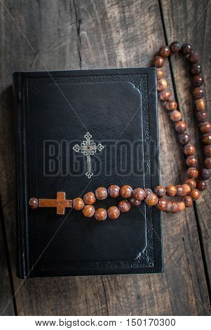 Wooden rosary beads and holy bible from above