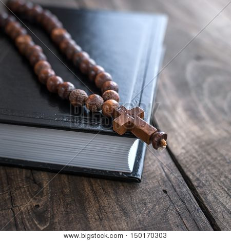 Close up photo of Wooden rosary beads and holy bible
