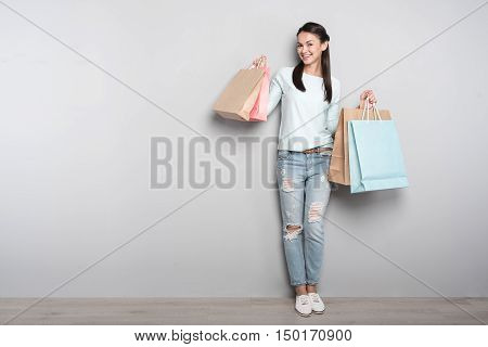 Stay in good mood. Delighted joyful smiling woman holding packages and resting after shopping while standing isolated on grey background