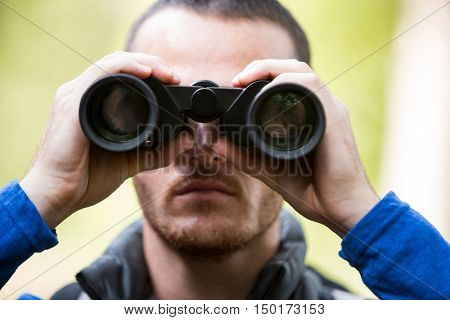 Close-up of male hiker looking through binoculars in forest