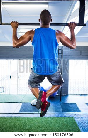 Rear view of male athlete doing chin-ups in fitness studio