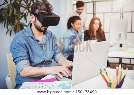 Businessman wearing virtual reality headset while using laptop against colleagues in creative office