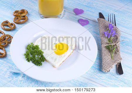 Fried egg in the shape of a heart a bouquet of flowers freshly squeezed orange juice. Breakfast for the beloved. romantic breakfast.
