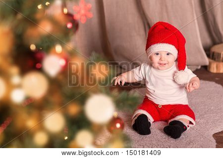 Beautiful little baby boy celebrates Christmas. New Year's holidays. Baby in a Christmas costume with gift christmas tree lights and red hat