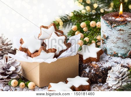 Christmas cookies in star shape and burning candle surrounded fir branches