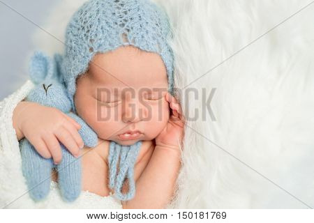 sleepy newborn boy in blue knitted hat with toy on white fluffy blanket