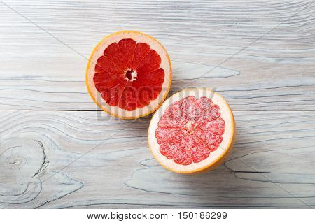 Sliced fresh ripe grapefruit over white natural aged wooden background