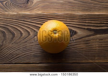 Perfect round fresh ripe grapefruit over brown natural aged wooden background