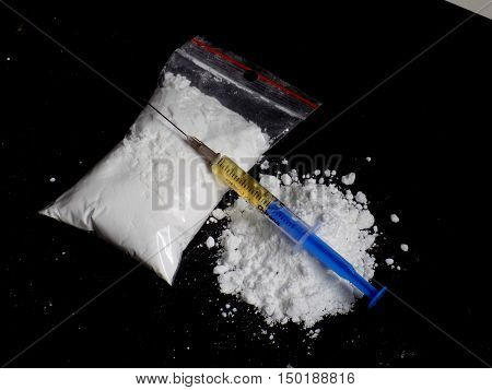 Injection syringe on cocaine drug powder pile and cocaine bag on black background