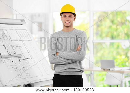 Young creative male engineer with helmet in design department