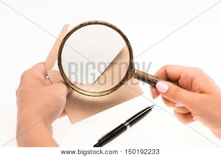 The female hands with envelope with magnifying glass on the white background