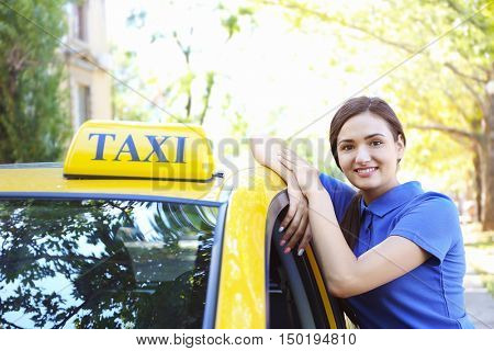 Beautiful female taxi driver standing near car