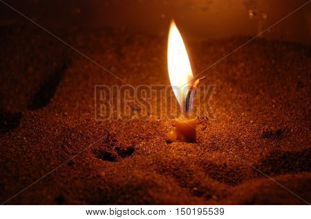 Church candle burning in sand. Symbol of religion hope and faith