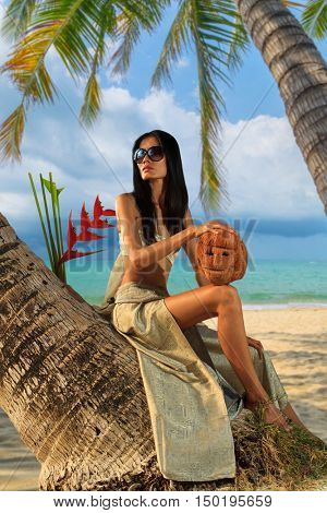 Woman sitting on a coconut tree on the tropical beach