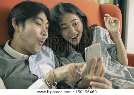 asian younger man and woman watching on smart phone with surprising and happiness faceinternet and social media concept