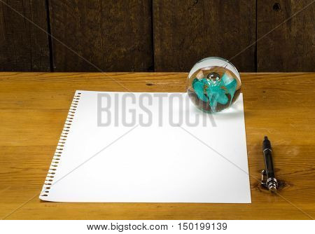 Blank piece of paper on pine wood table with paperweight and pen