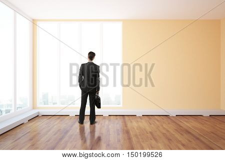 Back view of young businessperson with briefcase standing in unfurnished interior with wooden floor and panoramic windows with city view. 3D Rendering