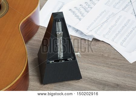 Black metronome with guitar and several notes on the wooden background