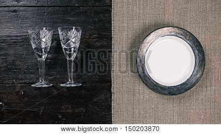 Still life with two empty wineglasses and plate on the half covered table. Flat lay