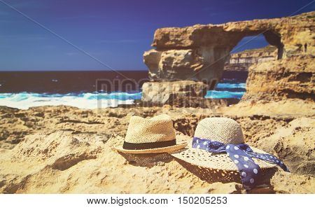two hats at Azure Window on Gozo island, romantic vacation in Malta concept