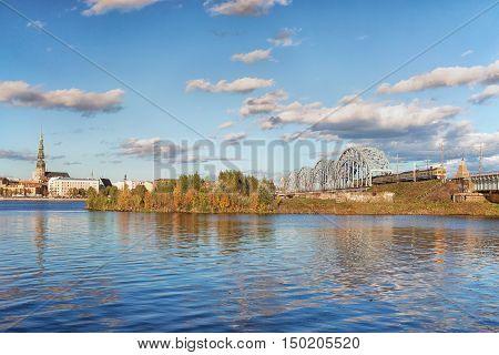 The train on the railway bridge over the river Daugava in Riga in autumn