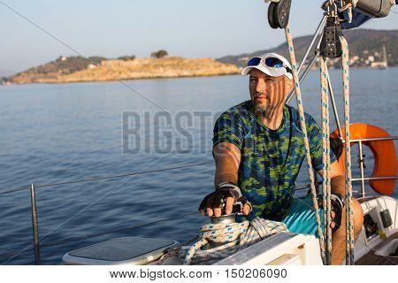 Skipper on his sail yacht. Sailing on the Sea.