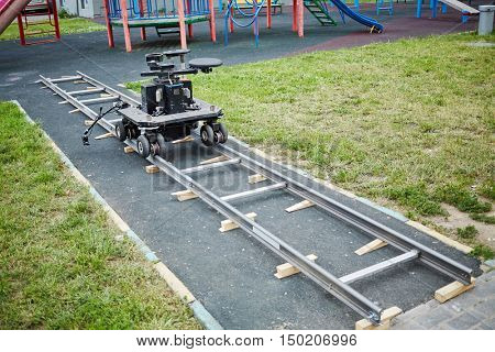 Cameraman dolly stands on rails mounted at children playground.