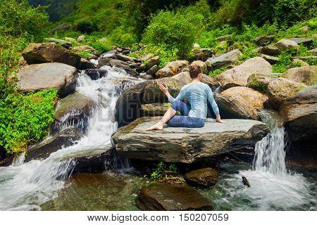 Yoga exercise outdoors - woman doing Ardha matsyendrasana asana - half spinal twist pose at tropical waterfall in Himalayas in India
