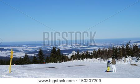 View from the peak of the Fichtelberg on the snowy Erzgebirge, winter landscape in Saxony, Germany, blue sky