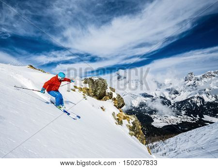 Skier skiing downhill in high mountains in fresh powder snow. San Martino di Castrozza in Italy.