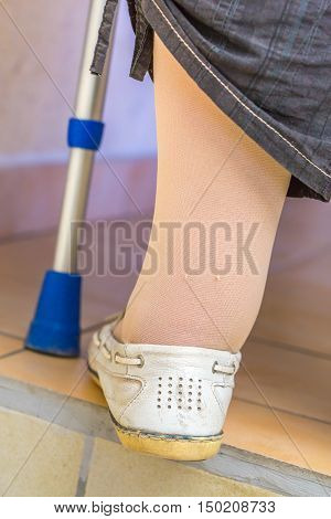 Age Woman With A Crutch Wearing Compression Stockings