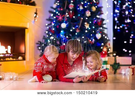 Children read a book and open gifts at fireplace on Christmas eve. Family with child celebrating Xmas. Decorated living room with tree fire place candles. Winter evening at home for parents and kids