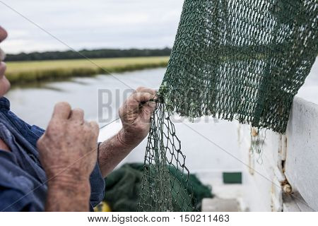 Weathered hands of fisherman mending net on a fishing boat