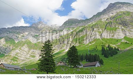 The Alpstein-massif in the Swiss Mountains, green mountain meadows with small huts, blue sky and white clouds