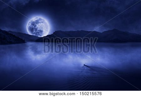 One boat run to the full moon at the dam with clouds and fog on water skin